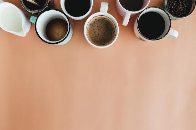 Несколько кофейных чашек, молока, зерен и молотого кофе в банке на бежевом фоне. фото высокого качества