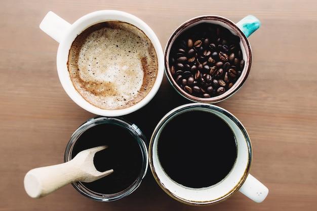 複数のコーヒーカップ、ミルク、豆、木製の背景の瓶に挽いたコーヒー。高品質の写真