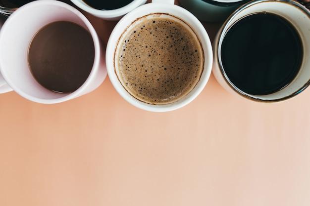 Несколько чашек кофе на бежевом фоне. фото высокого качества
