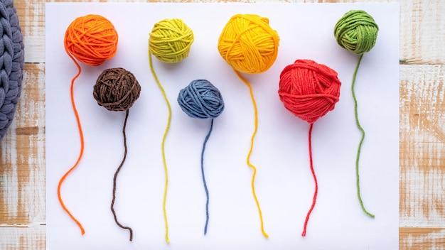 白い紙に複数の色の部分的に巻かれていない毛糸のボール。上面図