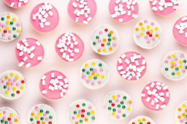 Несколько красочных красиво оформленных кексов на белом фоне, вид сверху.