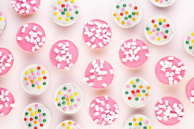 Несколько красочных красиво оформленных кексов на белом фоне