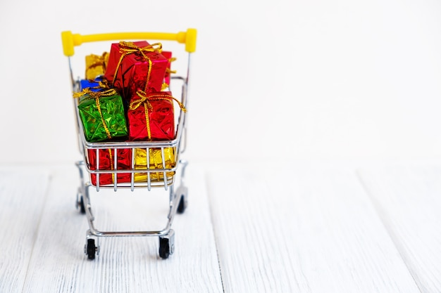 Multiple colors gift or presents boxes in a shopping cart, for sales promotion, rewards and christmas online shopping concept.