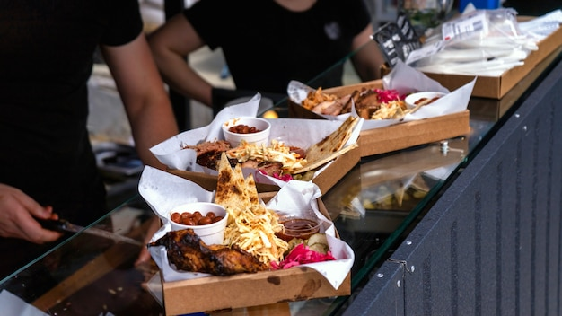 Multiple dishes with meal. meat and toppings. working cooks in food truck. street food