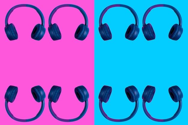 Несколько удвоенных беспроводных наушников на двухцветном фоне. плоский минималистичный стиль. дизайн и расцветки