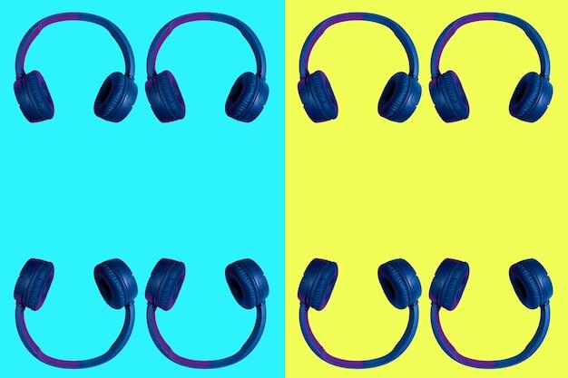 Несколько сдвоенных беспроводных наушников на ярком двухцветном фоне - голубом и желтом. плоский минималистичный стиль. дизайн и расцветки