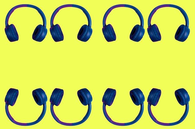 Множественные удвоенные беспроводные наушники на желтом фоне. плоский минималистичный стиль. дизайн и расцветки