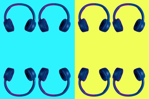 Multiple doubled wireless headphones on vivid two colored background in cyan and yellow. flat minimal style. design and colors