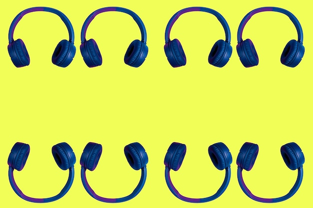 Multiple doubled wireless headphones on yellow background. flat minimal style. design and colors