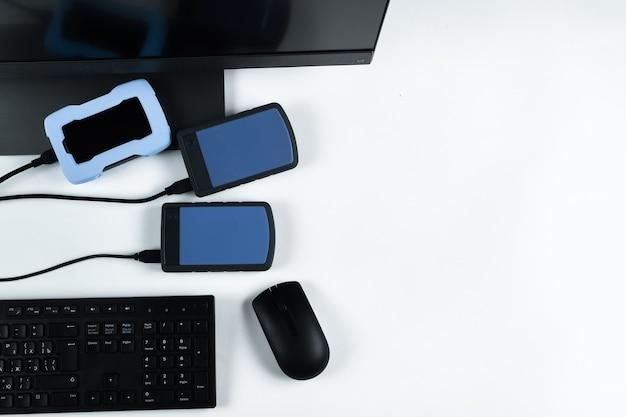 흰색 배경의 모노블록에 연결된 여러 개의 외장 하드 드라이브. 하드 드라이브가 있는 컴퓨터
