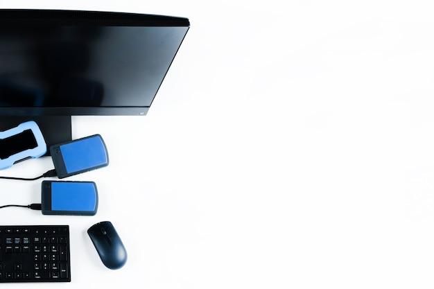Несколько внешних жестких дисков, подключенных к моноблоку на белом фоне.