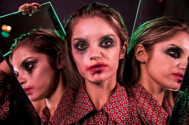 Многократный зеркальный эффект женщины, ухмыляющейся и смотрящей на камеру