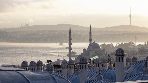 Multiple mosques, bosphorus strait, tv towers visible on the horizon, buildings located on the hills in istanbul, turkey