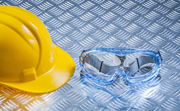 Multiple-purpose goggles building helmet on corrugated metal background construction concept