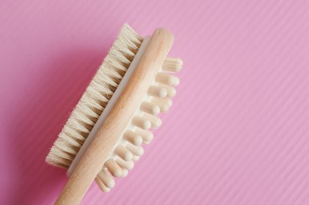 Многофункциональная деревянная щетка для массажа на розовом