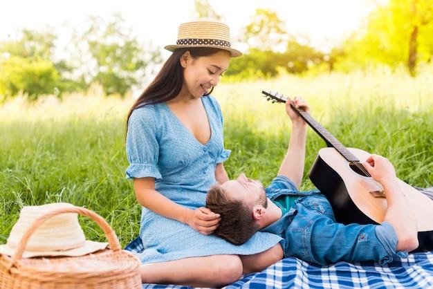 Multiracial adult couple enjoying guitar