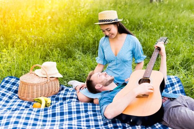 Multiracial adult couple having picnic