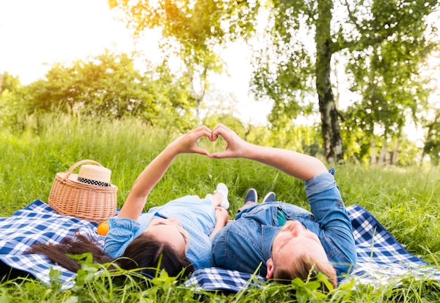 Multiracial adult couple making heart sign with fingers