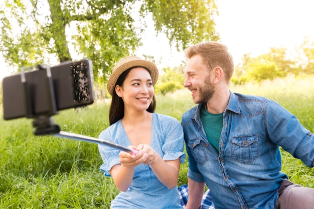 Multiracial adult couple taking selfie with smartphone