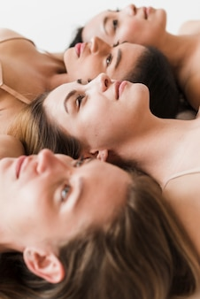 Multiracial beautiful young women lying together