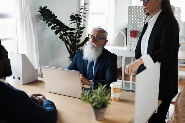 Многорасовые деловые люди, работающие в офисе банка - сосредоточены на старшем мужчине