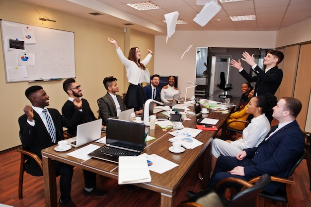 Multiracial business team meeting around boardroom table, two team leaders throw paper up.