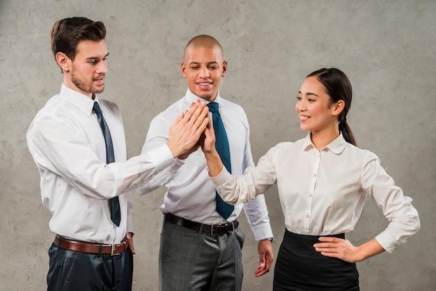 Многорасовые бизнесмены дают друг другу по пять штук перед серой стеной