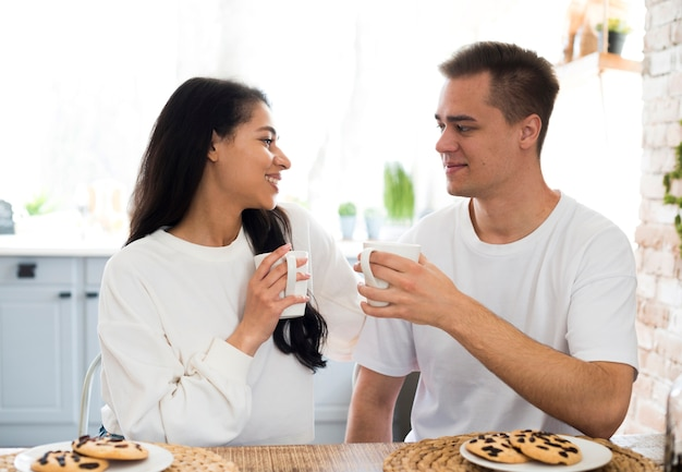 Multiracial couple drinking from cup at home