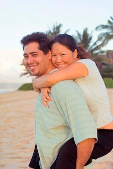 Multiracial couple embracing on hawaiian beach