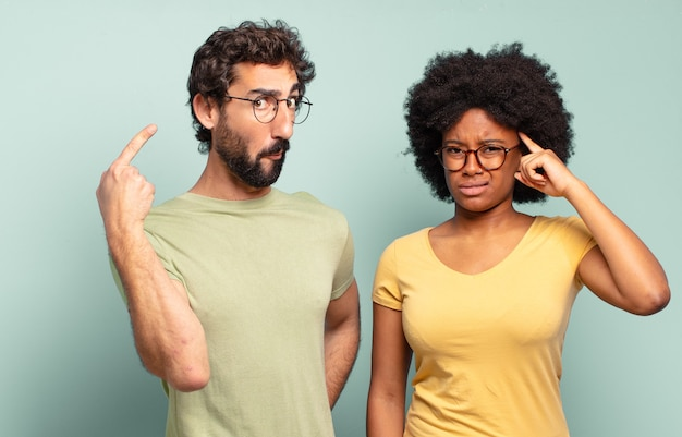 Multiracial couple of friends feeling confused and puzzled, showing you are insane, crazy or out of your mind