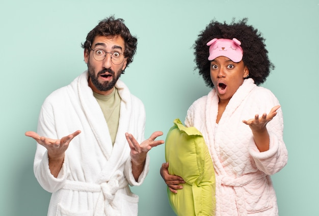 Multiracial couple of friends feeling extremely shocked and surprised, anxious and panicking, with a stressed and horrified look. pajamas and home concept