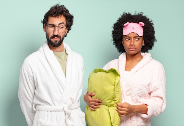 Multiracial couple of friends feeling sad, upset or angry and looking to the side with a negative attitude, frowning in disagreement. pajamas and home concept