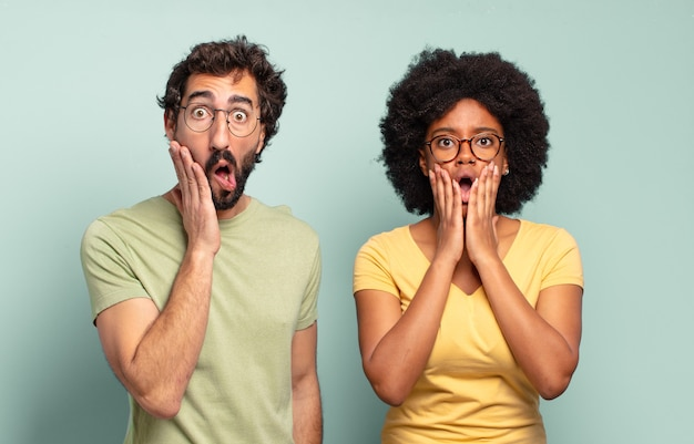 Multiracial couple of friends feeling shocked and scared, looking terrified with open mouth and hands on cheeks