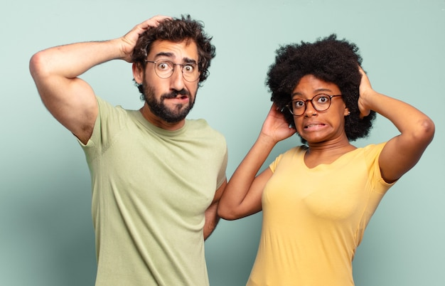 Multiracial couple of friends feeling stressed, worried, anxious or scared, with hands on head, panicking at mistake