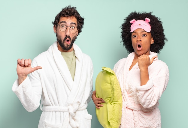 Multiracial couple of friends looking astonished in disbelief, pointing at object on the side and saying wow, unbelievable. pajamas and home concept