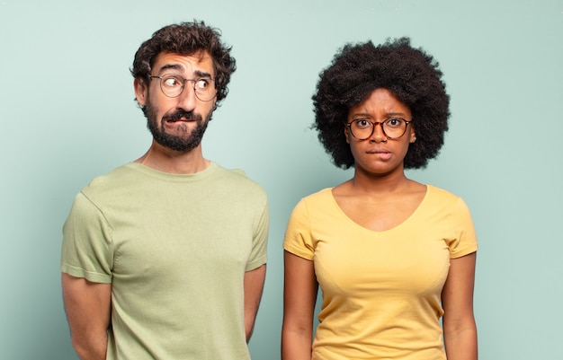 Multiracial couple of friends looking puzzled and confused, biting lip with a nervous gesture, not knowing the answer to the problem