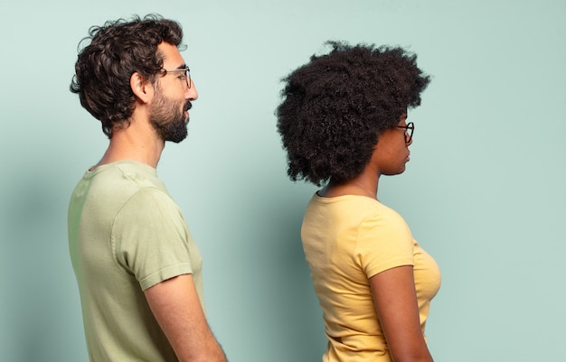 Multiracial couple of friends on profile view looking to copy space ahead