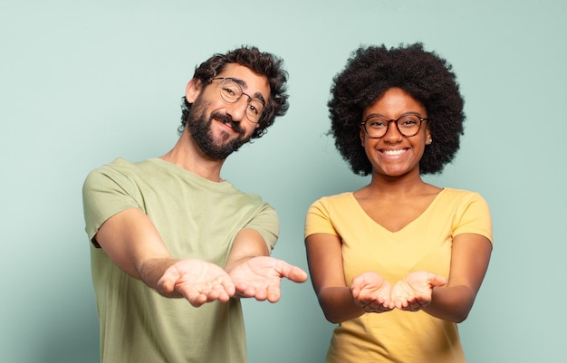 Multiracial couple of friends smiling happily with friendly, confident, positive look, offering and showing an object or concept