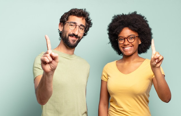 Multiracial couple of friends smiling and looking friendly, showing number one or first with hand forward, counting down