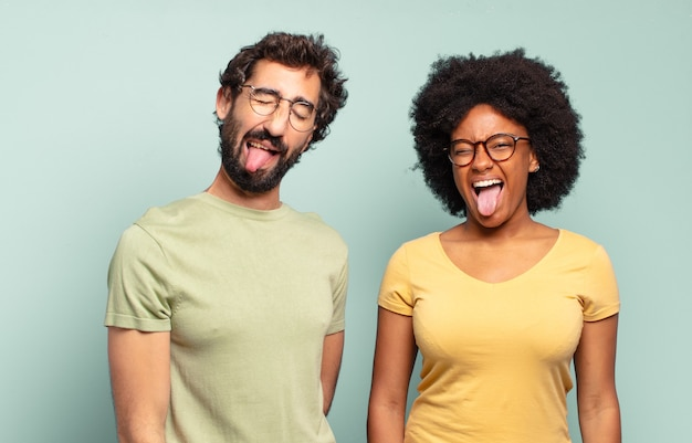 Multiracial couple of friends with cheerful, carefree, rebellious attitude, joking and sticking tongue out, having fun