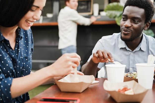 야외 푸드 트럭 레스토랑에서 즐거운 식사를 하는 다인종 커플 - 아프리카계 미국인 남자 얼굴에 초점