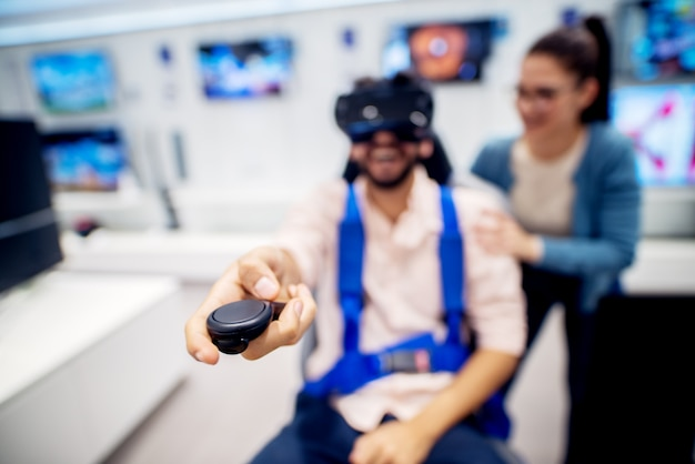 Multiracial couple having fun with vr goggles while boy sitting in the chair in the tech store. customer's service. shopping time.