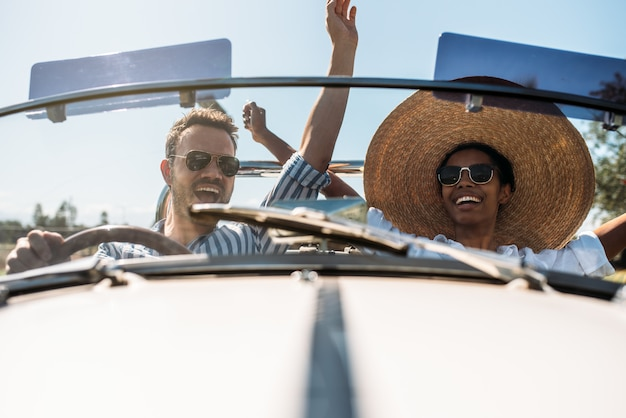 コンバーチブルヴィンテージ車で多民族のカップル