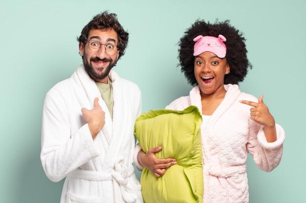 幸せ、驚き、誇りを感じ、興奮した驚きの表情で自分を指し示している多民族の友人のカップル。パジャマと家のコンセプト