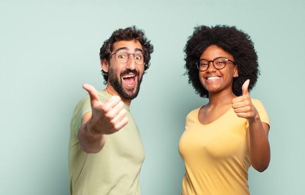 Многонациональная пара друзей чувствует себя гордой, беззаботной, уверенной и счастливой, позитивно улыбается и показывает палец вверх
