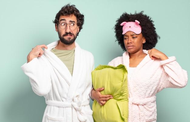 ストレス、不安、倦怠感、欲求不満を感じ、シャツの首を引っ張って、問題に不満を感じている多民族の友人のカップル。パジャマと家のコンセプト