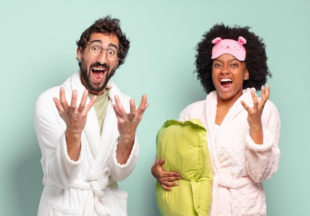 絶望的で欲求不満、ストレス、不幸、イライラ、叫び、叫び声を上げている多民族の友人のカップル。パジャマと家のコンセプト