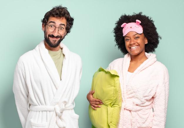 幸せそうに見えて嬉しそうに驚いて、魅了されてショックを受けた表情で興奮している多民族の友人のカップル。パジャマと家のコンセプト