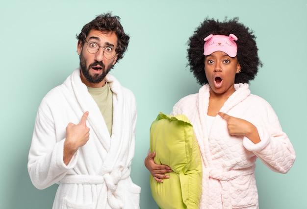 Многонациональная пара друзей выглядит шокированной и удивленной с широко открытым ртом, указывая на себя. пижамы и домашняя концепция