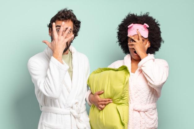 ショックを受けたり、怖がったり、恐怖を感じたり、顔を手で覆ったり、指の間を覗いたりしている多民族の友人のカップル。パジャマと家のコンセプト